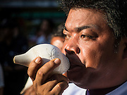 """04 SEPTEMBER 2015 - BANGKOK, THAILAND: An attendant to the Brahman priests blows a conch shell during a blessing ceremony in front of the Erawan Shrine Friday. A """"Holy Religious Ceremony for Wellness and Prosperity of our Nation and Thai People"""" was held Friday morning at Erawan Shrine. The ceremony was to regain confidence of the Thai people and foreign visitors, to preserve Thai religious customs and traditions and to promote peace and happiness inThailand. Repairs to Erawan Shrine were completed Thursday, Sept 3 after the shrine was bombed on August 17. Twenty people were killed in the bombing and more than 100 injured. The statue of the Four Faced Brahma in the shrine was damaged by shrapnel and a building at the shrine was damaged by debris.     PHOTO BY JACK KURTZ"""