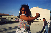 A grand-daughter of Pepe laFleur strikes a pose in their camping site. Saintes Maries de la Mer, Camargue France 1993. ...Roma Gypsies left Rajasthan in India a thousand years ago, in the ninth and tenth centuries. They were pushed west by the Ottoman Muslim Empire as it moved through Persia towards the frontiers of Europe. They entered Europe in the foutrteenth century and were slaves in Romania and Moldavia until the mid 1850s. There are about 15 million Roma gypries in the world, about 12 million who live in Europe. they are Europe's largest ethnic minority. They have rich traditions and culture, their own language. They are renowned for their prowess in music and dance; they are also skilled craftsman, metal roofmakers, silver and goldsmiths. Their traveling and nomadic lifestyle which grew from a necessity to find work, and because they were often moved on from one place to the next, has given them both a liberty but also marks them as different and they are often feared by sedentary peoples, who label and scapegoat them. They are hardy survivors and live in the brunt of racism and prejudice, often marginalised, living in poverty, without proper human rights afforded to them..