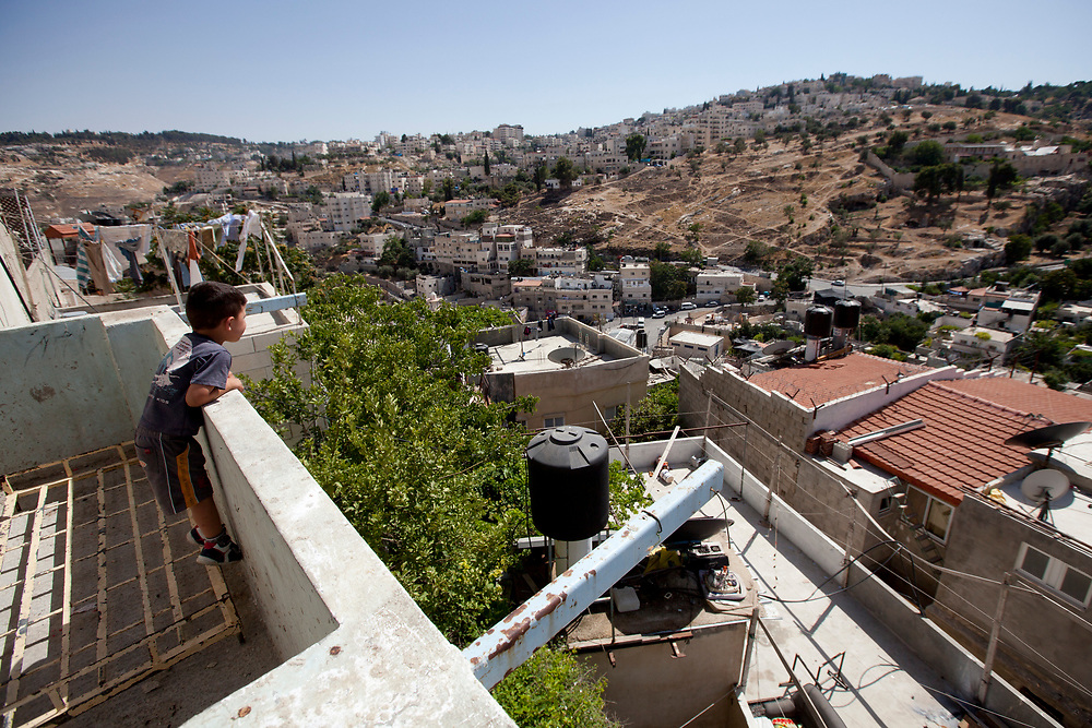 A Palestinian child looks over from the balcony of the Abu Nab house in the Arab East Jerusalem neighborhood of Silwan, June 28, 2010. The Abu Nab house served in the pre-state era as a synagogue, built in the 19th century for the small Yemenite community in Silwan. Jewish settlers backed by right-wing members of the Knesset threaten to hire private security firms to evict the four families living in the Abu Nab house.