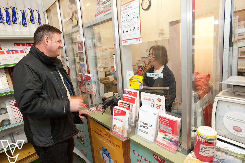 Pictured is postmaster Sarah Draisey serving customer Jeff Boardman<br /> <br /> Shireoaks Post Office, Worksop.  Community Fund feature.<br /> <br /> Date: December 1, 2014