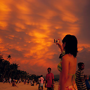Asian tourists during an amazing sunset at White Beach,  Boracay Island, the Philippines on October 7, 2008, Photo Tim Clayton....Asian tourists at White Beach, Boracay Island, the Philippines...The 4 km stretch of White beach on Boracay Island, the Philippines has been honoured as the best leisure destination in Asia beating popular destinations such as Bali in Indonesia and Sanya in China in a recent survey conducted by an International Travel Magazine with 2.2 million viewers taking part in the online poll...Last year, close to 600,000 visitors visited Boracay with South Korea providing 128,909 visitors followed by Japan, 35,294, USA, 13,362 and China 12,720...A popular destination for South Korean divers and honeymooners, Boracay is now attracting crowds of tourists from mainland China who are arriving in ever increasing numbers. In Asia, China has already overtaken Japan to become the largest source of outland travelers...Boracay's main attraction is 4 km of pristine powder fine white sand and the crystal clear azure water making it a popular destination for Scuba diving with nearly 20 dive centers along White beach. The stretch of shady palm trees separate the beach from the line of hotels, restaurants, bars and cafes. It's pulsating nightlife with the friendly locals make it increasingly popular with the asian tourists...The Boracay sailing boats provide endless tourist entertainment, particularly during the amazing sunsets when the silhouetted sails provide picture postcard scenes along the shoreline...Boracay Island is situated an hours flight from Manila and it's close proximity to South Korea, China, Taiwan and Japan means it is a growing destination for Asian tourists... By 2010, the island of Boracay expects to have 1,000,000 visitors.