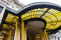 A porte cochere, portico or carriage entrance is a structure at an entrance to a building through which a  carriage or car can pass so that passengers can alight and be protected from the weather.  The porte-cochere was a feature of many 18th and 19th century buildings.