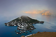 Thick fog seems to originate from the volcanic cone of Wizard Island, located in Crater Lake, Oregon. Crater Lake, the deepest fresh water lake in North America, is located in a caldera at the top of what was once Mount Mazama. A massive eruption around 5,700 B.C. caused the mountain to collapse. While the Wizard Island cone is long dormant, there is some hydrothermal activity at the bottom of Crater Lake, suggesting the mountain is still active.
