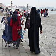 """VENICE, ITALY - JUNE 01:  Women wearing veils and burqua walks just few yards away of Flavio Lucchini's  exhibition """"What Women Want (?)"""" on June 1, 2011 in Venice, Italy. The exhibition addresses the controversiat theme of the burqa  (Photo by Marco Secchi/Getty Images)"""