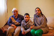Portrait of mother Gabriela Costache (37, left), son Alberto (8) and 17 years old daughter in law Maria Bondaret in their living room at home.