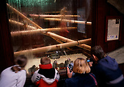 A913P9 Children looking at and photographing spider monkeys through a clear glass wall, Colchester zoo, Essex, England