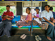 25 NOVEMBER 2017 - YANGON, MYANMAR: Passengers on the Yangon Circular Train. The Yangon Circular Train is a 45.9-kilometre (28.5 mi) 39-station two track loop system connects satellite towns and suburban areas to downtown. The train was built during the British colonial period, the second track was built in 1954. Trains currently run both directions (clockwise and counter-clockwise) around the city. The trains are the least expensive way to get across Yangon and they are very popular with Yangon's working class. About 100,000 people ride the train every day. A a ticket costs 200 Kyat (about .17¢ US) for the entire 28.5 mile loop.    PHOTO BY JACK KURTZ