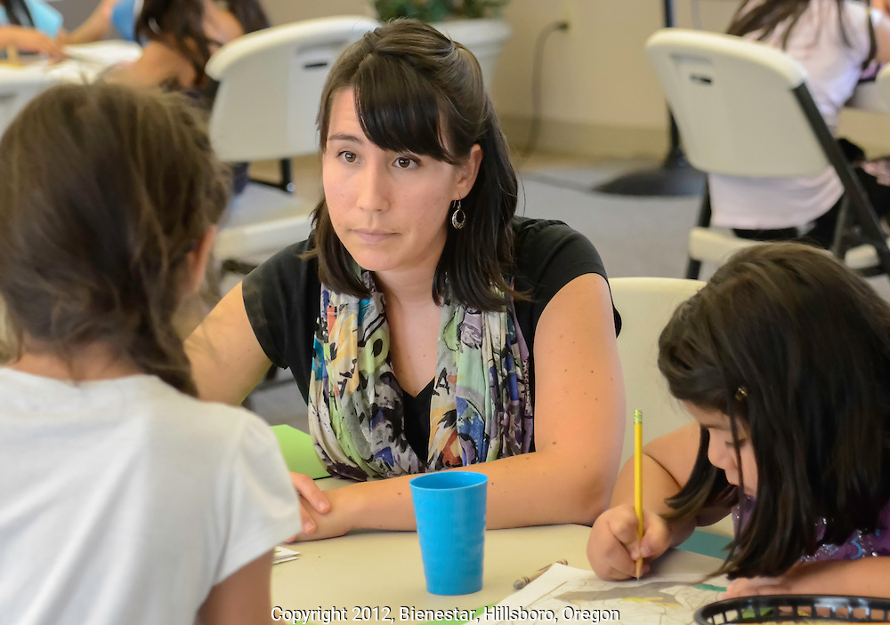 A teacher helps children of farm workers study in an after-school homework club.