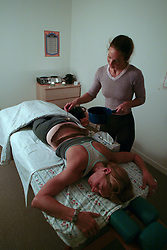 Barbora Maravkova, top, spreads oil on the back of Karla Rodebush during an Indian treatment known as ayurveda at Emeryville Health and Wellness Center, Wednesday, Sept. 24, 2003 in Emeryville, Calif.  The dam on Rodebush's back is made of bread dough, and the oil works into the skin and nourishes the underlying tissue (D. Ross Cameron/The Oakland Tribune)