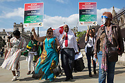 Windrush campaigners arrive in Parliament Square after marching from the Home Office to deliver a letter to the House of Commons on 23rd June 2021 in London, United Kingdom. The campaigners are calling for a new independent body, and not the Home Office, to administer the scheme intended by the government to compensate them for the violation of their rights. Many legal residents who came to the UK from the Caribbean lost their homes, jobs and other rights after having been targeted by the Home Office.
