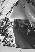 Skier on Central Rongbuk glacier climbs towards base of West ridge under North face Chomolungma , Mt Everest, Tibet