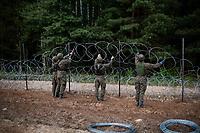 Wies Nomiki, woj. podlaskie, 25.08.2021. Rozpoczela sie budowa 2,5-metrowego plotu z drutu kolczastego na granicy z Bialorusia. N/z wojsko buduje plot na pasie ziemi granicznej fot Michal Kosc / AGENCJA WSCHOD