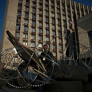 A separatist mans the barricades surrounding a government building in Donetsk.