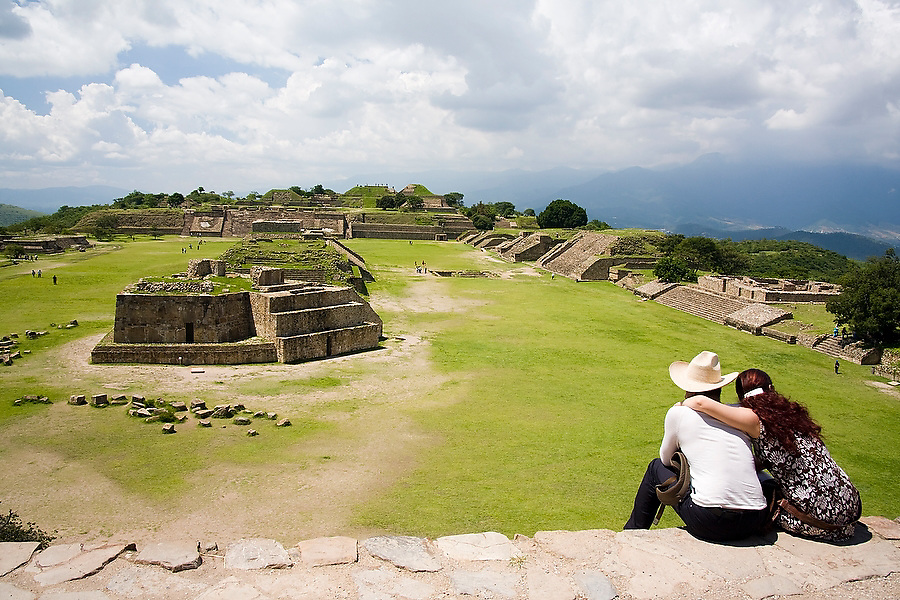 A young couple sits on a stone step looking out over the Zapotec ruins of Monte Alban, Oaxaca state, Mexico on July 17, 2008.
