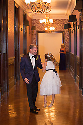 father and daughter dancing together in a hallway at a formal party