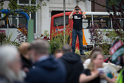 "© Licensed to London News Pictures . 23/05/2015 . Manchester , UK . A man wearing a "" Still hate Thatcher "" t shirt photographs a demonstration , organised by "" The People's Assembly "" , against austerity in Piccadilly Gardens in Central Manchester , attended by approximately 2000 people . Photo credit : Joel Goodman/LNP"
