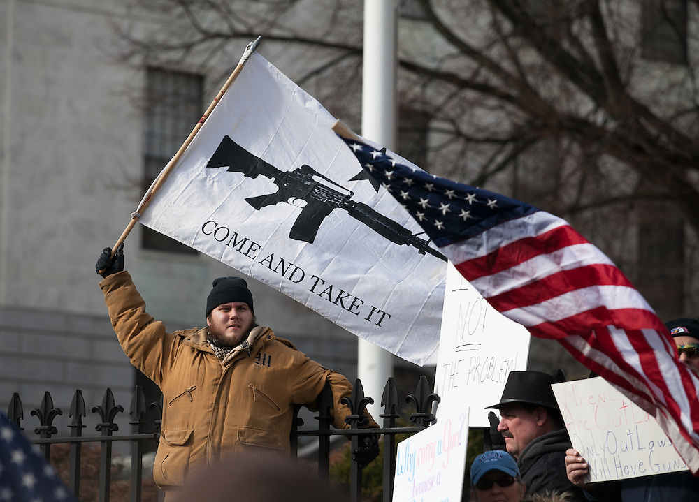"""Boston, MA 01/19/2013.Nick Marchesi of Boston waves a """"Come And Take It"""" flag with the image of an AR-15 during Saturday's protest at the Massachusetts State House, part of a coordinated nationwide movement against proposed gun control legislation..Alex Jones / www.alexjonesphoto.com"""