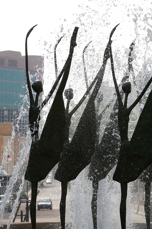 """Still Point ballerina sculpture near the Ritz-Carlton in St. Louis, Missouri.  The sculpture is bronze and features six dancers, each 12 feet tall, performing in a fountain of water. The ballerinas are posed in a classical ballet position: """"grand battement"""".  The sculpture was created by Ruth Keller Schweiss."""