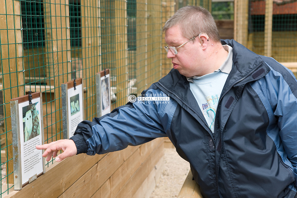 Man with learning disabilities reading sign outside a bird cage on a trip to an animal centre,