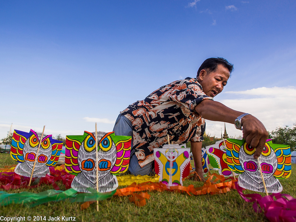 """24 JULY 2014 - BANGKOK, THAILAND: A kite vendor sets up his kites on Sanam Luang during the happiness party. People bought and flew kites during the party. The Thai Junta is organizing a series of public events throughout Thailand meant to bolster public opinion. The events are called """"restoring happiness to the people"""" parties. They feature historic pageants, music, food, health checks and free haircuts. The party in Bangkok is on Sanam Luang, the Royal Parade Ground, which is near the Grand Palace and the Ministry of Defense.    PHOTO BY JACK KURTZ"""