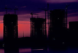 Stock photo of the silhouette of ongoing building construction late in the evening