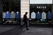 Reiss shop suits on display in a central London window.