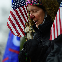 HARRISBURG, PA:  Jericho Marchers, supporters of President Donald Trump, pray while holding an effigy of the Virgin Mary after marching in protest around the Pennsylvania State Capitol as state electors meet to officially cast their Electoral College vote in Harrisburg, PA on December 14, 2020.  The Keystone State's 20 electoral votes propelled Joe Biden past the 270 electoral votes needed for the presidency.  CREDIT:  Mark Makela for The New York Times