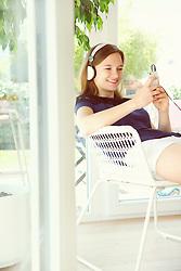 Teenage Girl Wearing Headphones Using Smartphone
