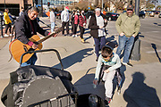 31 OCTOBER 2020 - DES MOINES, IOWA: RANDY KONG, a Des Moines busker, performs while people in line to vote at the Polk County Auditor's Office drop money into his tip jar. This is the last weekend of early voting before the 2020 US presidential election. An elections official said that by November 3, which is Election Day, about 45 percent of the registered voters in Polk County will have already voted.     PHOTO BY JACK KURTZ