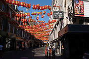 Lisle Street in Chinatown remains very quiet with a few people visiting Chinese restaurants to pick up food and to see the red lanterns on 25th June 2020 in London, England, United Kingdom. As the July deadline approaces and government will relax its lockdown rules further, the West End remains quiet, while some non-essential shops are allowed to open with individual shops setting up social distancing systems.