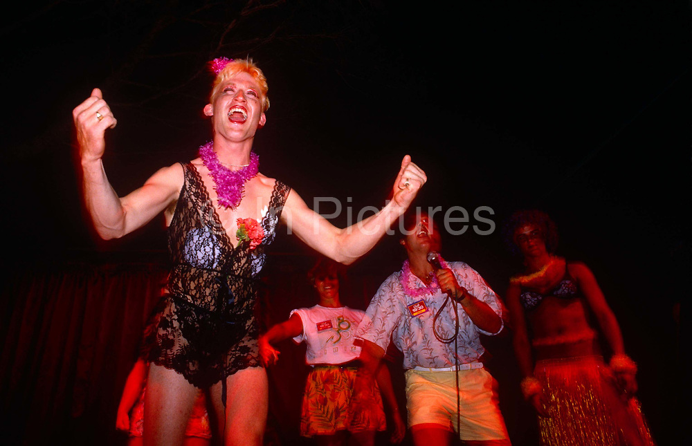 """Young men in drag perform to an audience as part of their Club 18-30 holiday experience to Ibiza, Spain. A tour rep encourages the men to push their inibitions to the limit but with a reputation for 'Sun, Sand and Sex' the 18-30 holiday formula has been labelled as parents' worth nightmare. From from the company's web site however the fantasy sounds less riotous: """"There comes a time in life when you need to do it for yourself. A time to break free and break the mould. To explore, leave the map at home and find yourself. To find that one moment and make it last a lifetime. That time is now. Sunrise to sunset. Sunset to sunrise. This is the time of your life. Love every single second of it."""""""