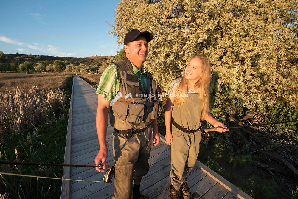 Father and daughter in waders walking together and smiling on footbridge while fly fishing Billingsley Creek Wildlife Managment area in Hagerman, Idaho. MR