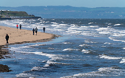 Portobello beach and promenade near Edinburgh during Coronavirus lockdown on 19 April 2020. People walking on beach with strong wind causing waves in Firth of Forth.