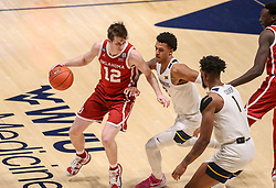 Feb 13, 2021; Morgantown, West Virginia, USA; Oklahoma Sooners guard Austin Reaves (12) dribbles against West Virginia Mountaineers forward Jalen Bridges (2) during the second half at WVU Coliseum. Mandatory Credit: Ben Queen-USA TODAY Sports