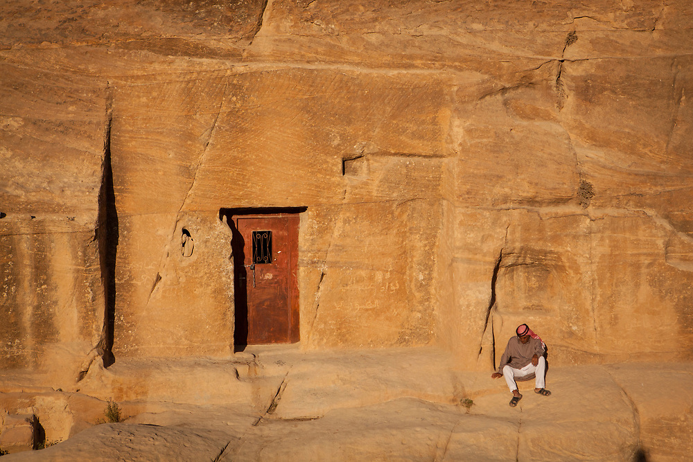 Bedouin man sitting in front of a sandstone rockface with a door cut into it. Part of the Petra, Jordan complex.