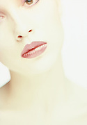 Washed out, very pale, close up photo of young woman's face against a white background