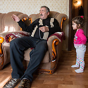 CAPTION: Stella and Safira's grandfather takes an active role in their lives. He and his wife both live with the family, and as his daughter-in-law Armena has her hands full with the children, his son Arman is the sole breadwinner for all six people. Without Russian State medical insurance, it would therefore be very difficult for the family to afford Stella's surgery, so it's a great relief for them that SmileTrain is able to step in. LOCATION: Volgograd, Russia. INDIVIDUAL(S) PHOTOGRAPHED: Vachagan Aharonyan (left) and Safira Aharonyan (right).