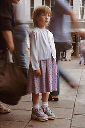 Young girl standing in middle of busy street looking lost,