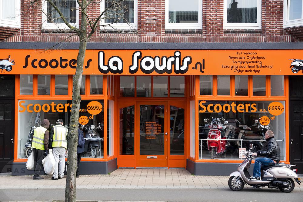 In Utrecht kijken voorbijgangers, waaronder enkele straatvegers, verlekkerd naar scooters in een etalage van een scooterwinkel.<br /> <br /> In Utrecht passers are looking through a window at scooters in a shop.