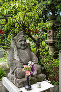 A statue of Ebisu, one of the Seven Gods of Fortune at the Toyokawa Inari Betsuin temple in Asakusa, Tokyo, Japan. The Buddhist temple is part of the Soto Zen sect and enshrines the deity Toyokawa Dakinishinten but also known for the thousands of fox statues.