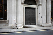 Woman walking her small dog along Threadneedle Street in the City of London, United Kingdom.