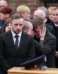 © Licensed to London News Pictures. 22/03/2016. Belfast, Northern Ireland, UK. Mourners comfort each other as the funeral of murdered prison officer Adrian Ismay at  Woodvale Methodist church. Mr Ismay died following a booby-trap bomb that exploded under his van in East Belfast on March 4th. Photo credit: Peter Morrison/LNP