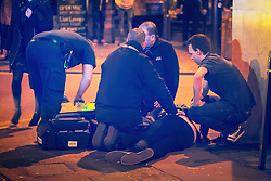 """© Licensed to London News Pictures . 19/12/2015 . Manchester , UK . Paramedics attend to a man lying on the pavement in the city's Northern Quarter . Revellers in Manchester enjoy """" Mad Friday """" - also known as """" Black Eye Friday """" - the day on which emergency services in Britain are typically at their busiest , as people head out for parties and drinks to celebrate Christmas . Photo credit : Joel Goodman/LNP"""