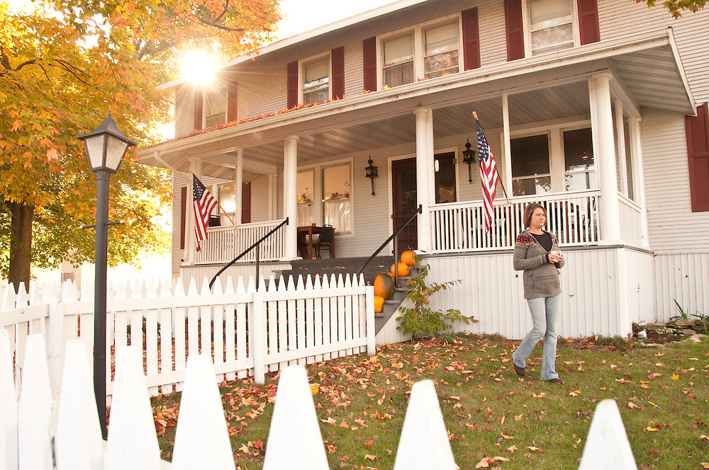 Exterior of the Nahma Inn with fall color American flag and picket fence in Nahma Michigan.