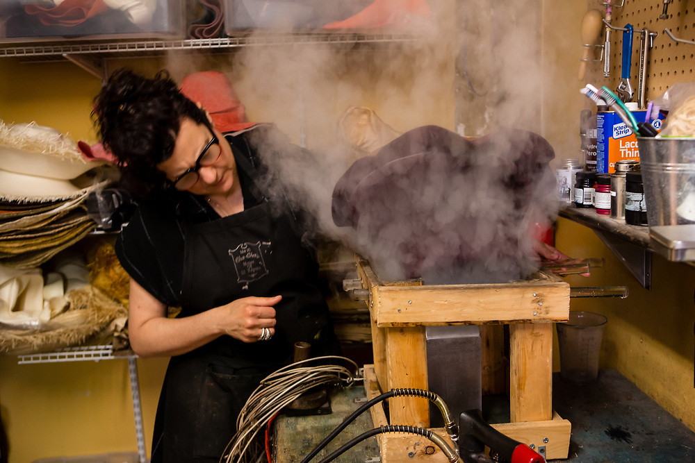 A partially-shaped felt hat over the steam generator, being re-steamed for further shaping.