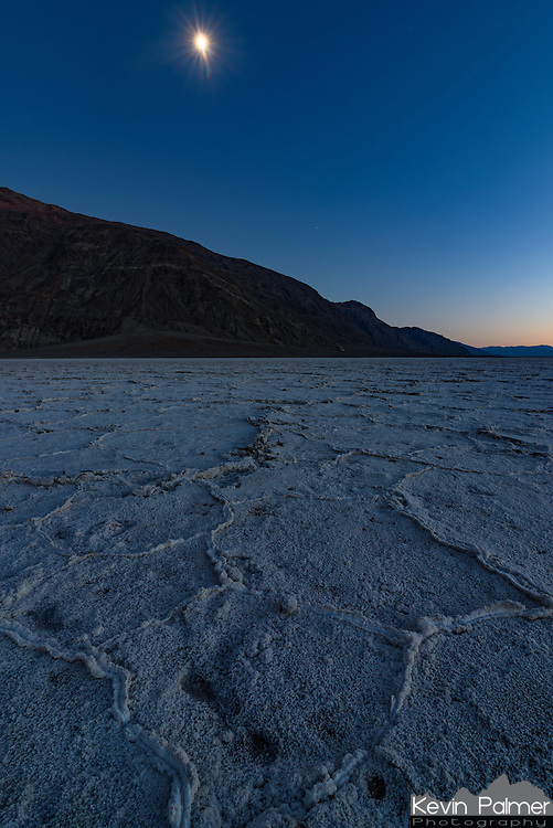 The moon glows above the salt flats at Badwater Basin during twilight.