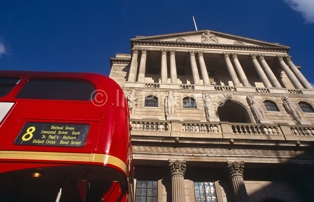Looking upwards towards the back of a number 8 red London bus which passes the pillars of the famous Bank of England building at Cornhill in the City Of London, the financial district, otherwise known as the Square Mile. We see the Bank rising as an imposing classical structure. Its columns are converging because of wide-angle lens-distortion, giving us the image of strength, stability and influence in UK economics. The bus is a traditional design called a Routemaster which has been in service on the capital's roads since 1954 and is nowadays only seen on heritage routes. Its distinctive rounded rear bodywork is easily recognisable as that classic British icon.