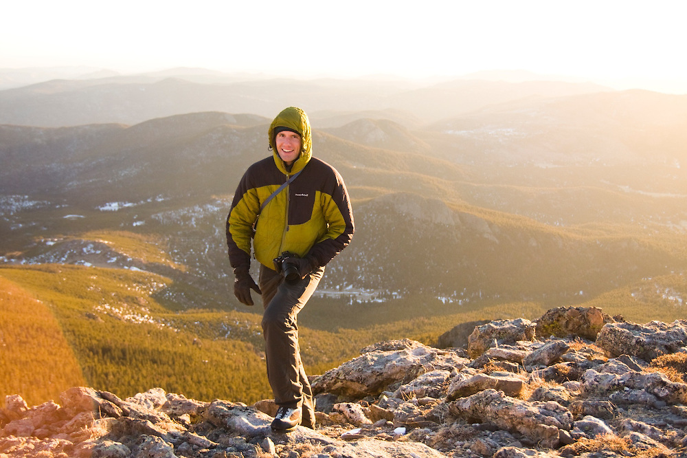 Obadiah Reid on the summit of Twin Sisters Mountain at sunrise in Rocky Mountain National Park, Colorado. The rolling hills of the Front Range extend behind him towards the plains.