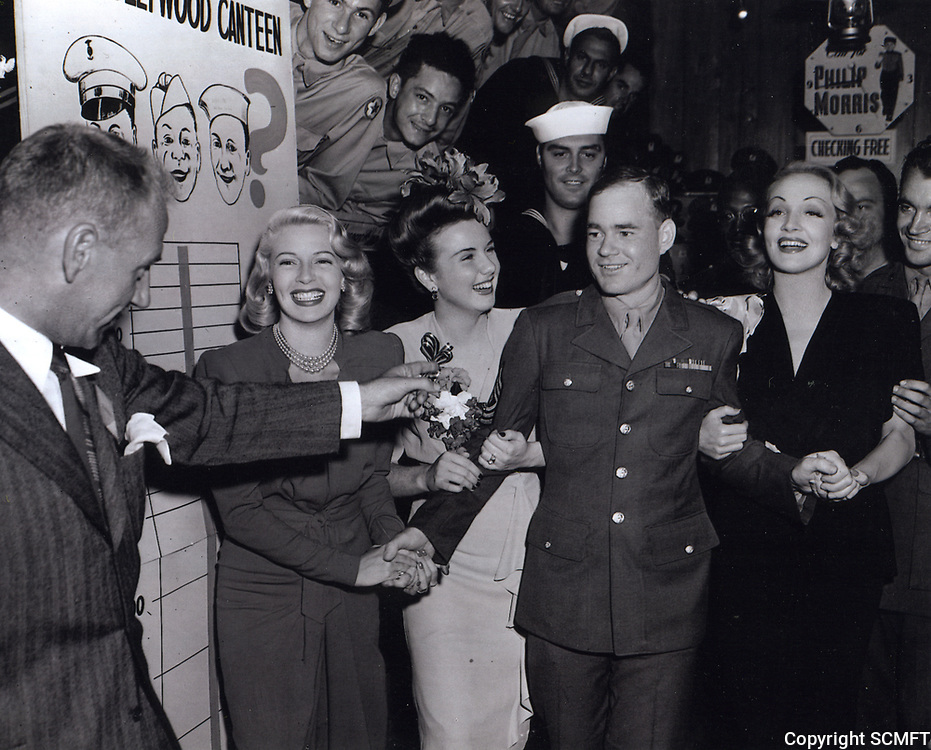 1943 (L to R) Lana Turner, Deanna Durbin, and Marlene Dietrich greet Sgt. Carl Bell as the millionth man to visit the Hollywood Canteen