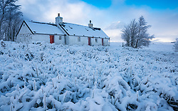 Snow covered Blackrock Cottage with mist covered Buachaille Etive Mor in the distance in winter, Glen Coe , Scotland, UK